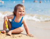Little child girl in blue swimsuit is playing on the beach near blue sea - 152997562