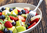 Bowl of fruits salad with strawberries, blueberries, apples, kiwi, bananas in slices, healthy seasonal summer fruits salad assortment