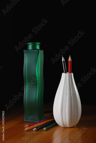 green glass and white ceramic vases with pencils on the wooden table