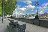 Chelsea Embankment on the River Thames and Albert Bridge with summery, blue, cloud flecked sky.