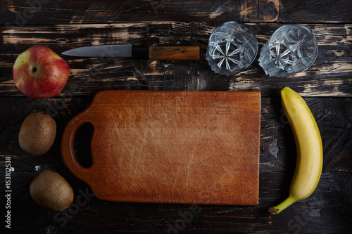 Fresh fruits on a board on a wooden background. View from above. Banana, orange, kiwi, apple. Useful fruits.