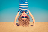 Funny child standing upside down on sandy beach - 153140321