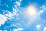 Sunny background, blue sky with white clouds and sun - 153160381