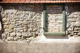 Rustikale Mauer mit Fensterrahmen / Eine rustikale Mauer aus versetzten und abgebrochenen Steinen mit Dachziegeln und einem zugemauerten Fensterrahmen.