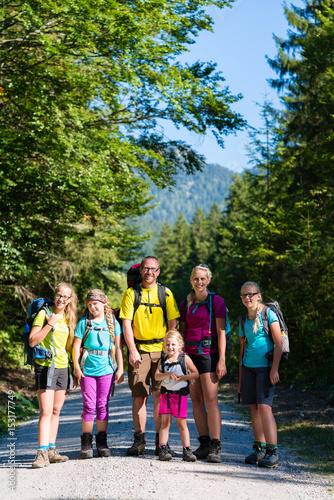 Familie mit vier Kindern beim Wandern in den Bergen Poster