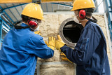 Workers applying insulation material to an industrial boiler - 153179356