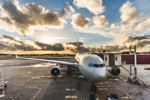 Fototapeta Airplane boarding passengers at airport at sunset