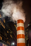 Smoke stack on street in New York City with skyscraper in background