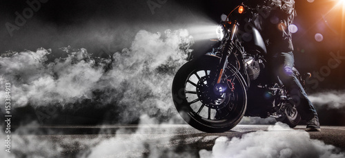Close-up of high power motorcycle chopper with man rider at night