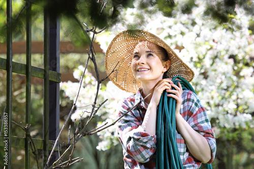 Poster Mój piękny ogród, szczęśliwa kobieta przygląda się rozkwitającym roślinom