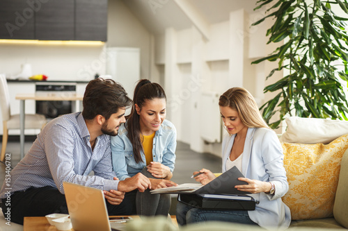 Leinwandbild Motiv Female Real Estate agent offer home ownership and life insurance to young couple.