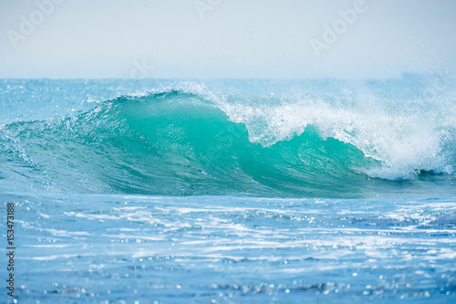 Blue wave in tropical ocean. Wave crashing in sunny day