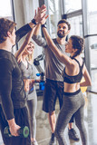 Happy young athletic people in sportswear giving high five in gym - 153483598