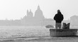 VENICE, ITALY - MARCH 14, 2014: Fisherman from Riva S. Biagio waterfront and silhouette of Santa Maria della Salute church.