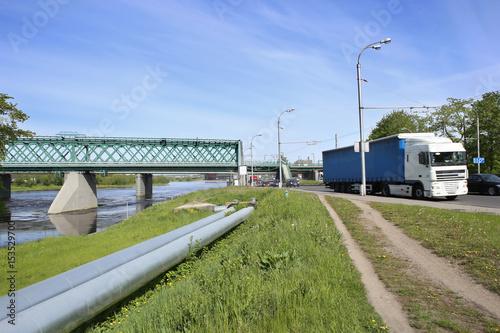 Foto op Plexiglas Havana Transportation in city: railway bridge, industrial pipes and road transport. Kaunas, Lithuania – May 17, 2017: Industrial landscape with Green Railway Bridge.