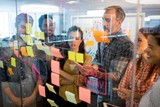 Creative business team looking at sticky notes on glass window - 153538369