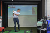 young man playing golf and interacting with a video-game