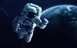 Astronaut in front of the Earth planet. Elements of this image furnished by NASA