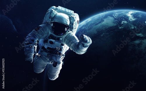 Astronaut in front of the Earth planet. Elements of this image furnished by NASA - 153602925