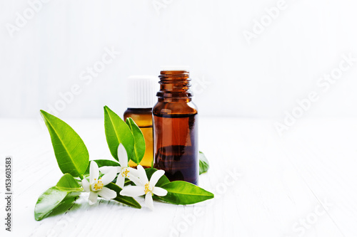 Plakat Neroli (Citrus aurantium) essential oil in a brown glass bottle with fresh white  flowers on ligth background