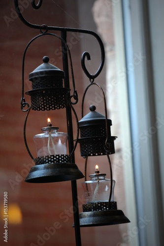 Two oil lanterns hanging from hooks in a rack Two oil lamps lighted with lanterns hanging from a steel rack, with cobwebs on the rack