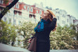A woman in a European city  walks in a black coat at autumn and examines the neighborhood