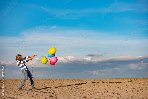 Woman with toy balloons in windy weather