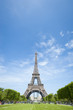 Bright daytime scenic view of the Eiffel Tower in Paris, France, with spring greenery on the Champs de Mars under clear blue sky