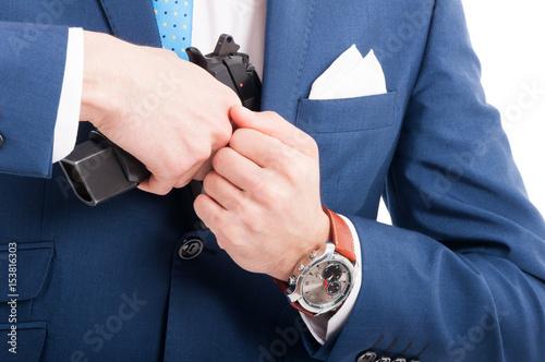 Man drawing his gun from coat pocket