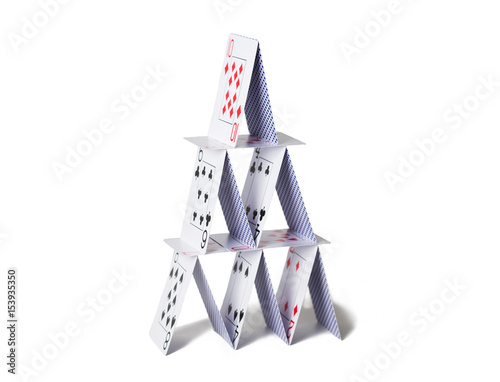 house of playing cards over white background плакат