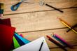 Schreibtisch mit Anspitzer, Tonpapier und Buntstiften von oben auf holz
