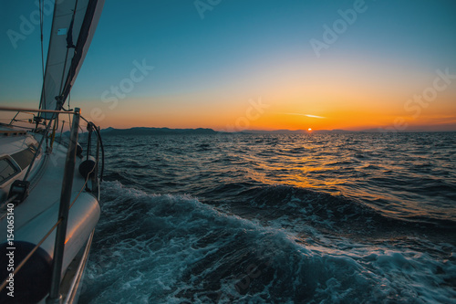 Sailing yacht glides through the waves of the sea during a magical sunset.