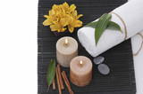 Spa setting with candle, towel stones, leaf on mat