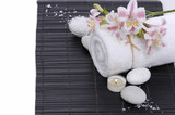 Spa setting with candle, towel ,orchid, ,salt in bowl on mat