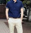 Молодой красивый мужчина позирует в синей рубашке, светлых летних штанах и часах