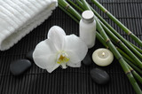 Spa setting with candle ,orchid ,towel ,stones ,grove on mat
