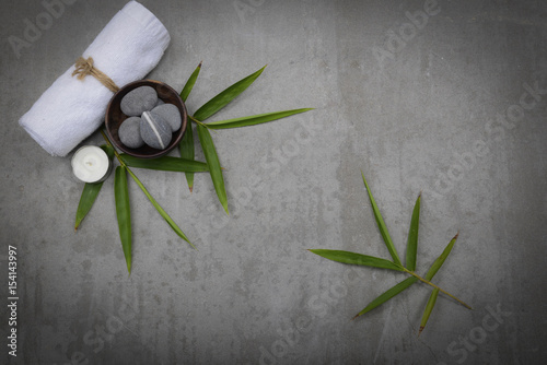 Tuinposter Spa Gray stones in bowl with bamboo leaf,towel, candle -gray background