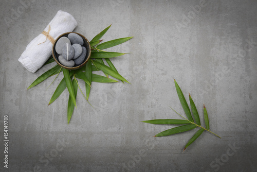 Plexiglas Spa Gray stones in bowl with bamboo leaf,towel gray background