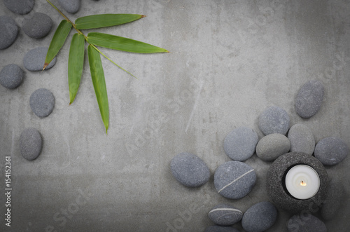 Plexiglas Spa bamboo leaf, with pile of gray stones, with candle -gray background