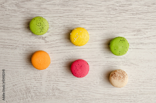 Top view of six multi colored macarons, light wooden table Poster