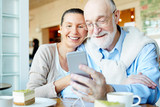 Affectionate couple with smartphone having nice leisure in cafe - 154184995