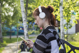 A girl in a park on a bench listening to music on a smartphone or player with headphones