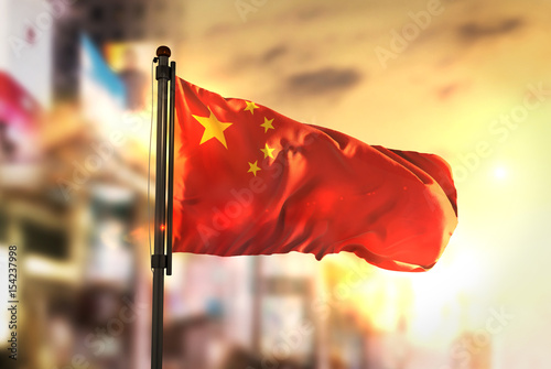 China Flag Against City Blurred Background At Sunrise Backlight Poster