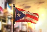 Fototapety Puerto Rico Flag Against City Blurred Background At Sunrise Backlight