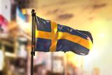 Sweden Flag Against City Blurred Background At Sunrise Backlight