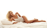Sensual, blond lady laying on the soft bed