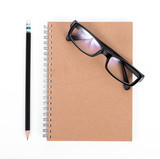 Blank diary, pencil, and glasses on white background