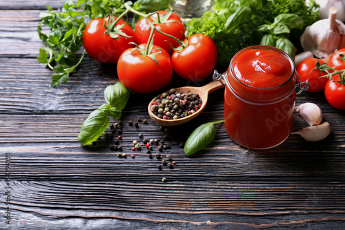 Composition of ketchup in jar and ingredients on wooden background