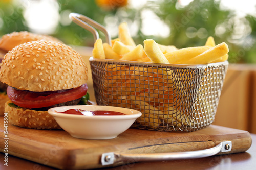 Poster Fast food burger with french fries on a wooden board