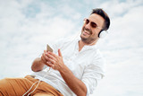 Handsome young man with white headphones outside